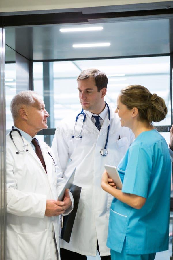 Doktorer och kirurg som påverkar varandra med de i hiss royaltyfri fotografi