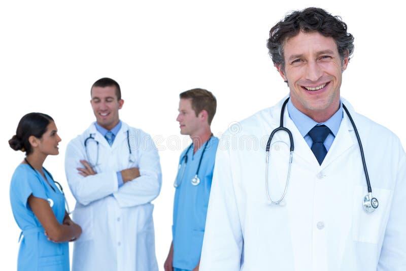 Doktorer och sjuksköterskor med armar korsat diskutera royaltyfri foto