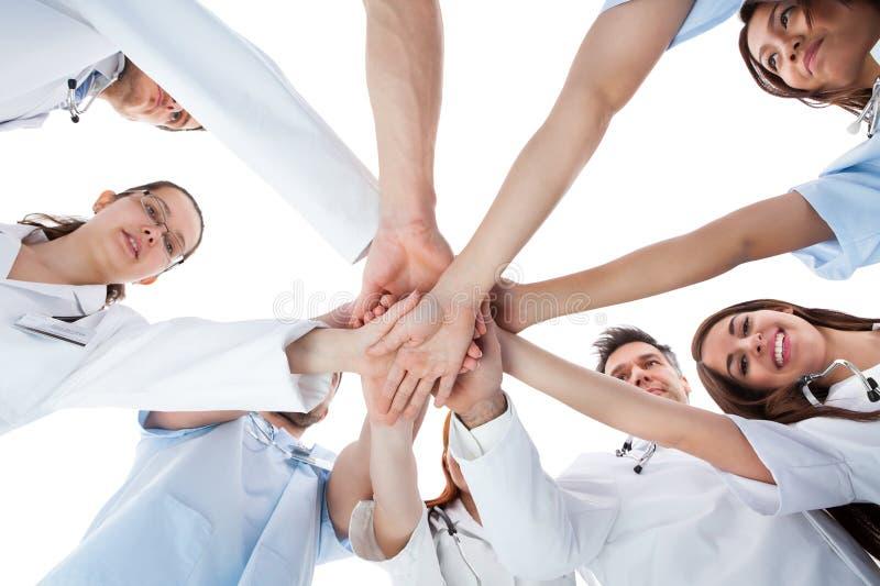 Doktorer och sjuksköterskor som staplar händer