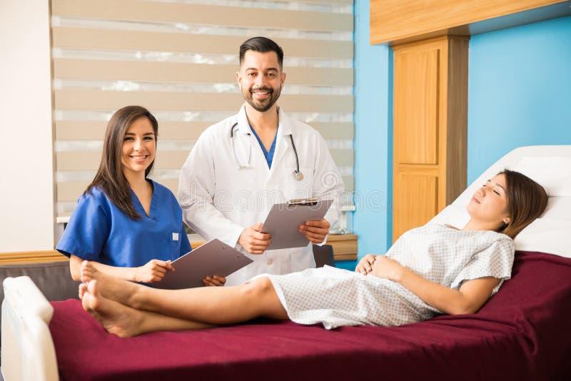 Doktorer som besöker patienter i ett sjukhus fotografering för bildbyråer