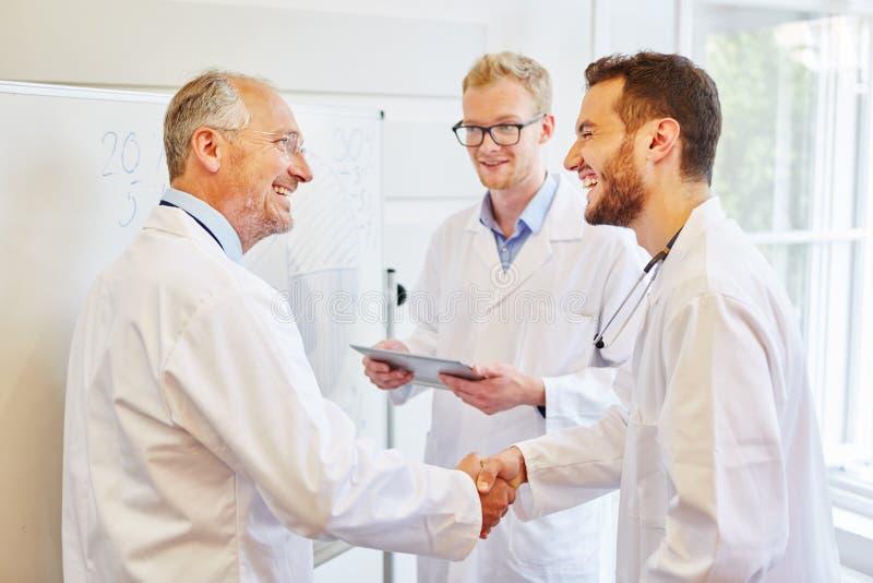 Doktorer som delar handschake arkivbilder