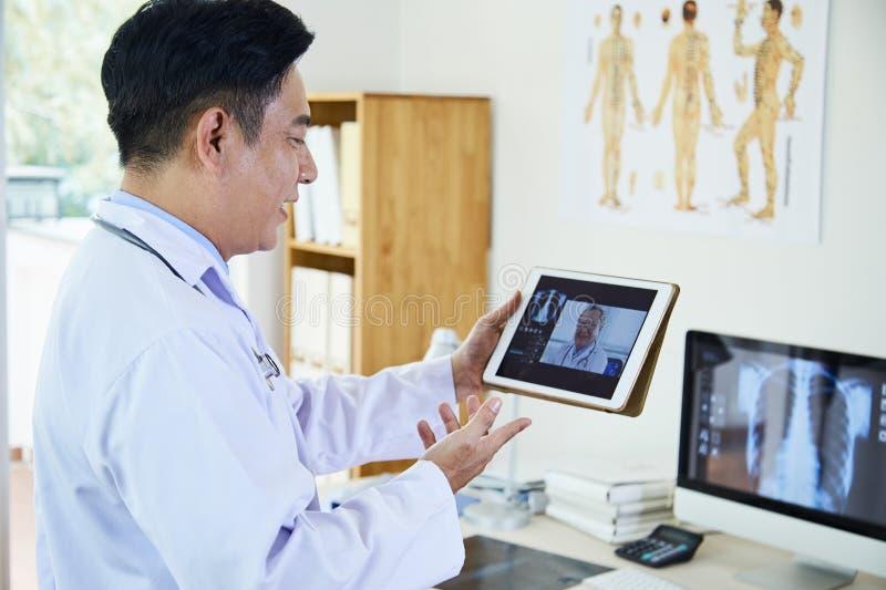 Doktorer som direktanslutet diskuterar röntgenstrålebild royaltyfri bild