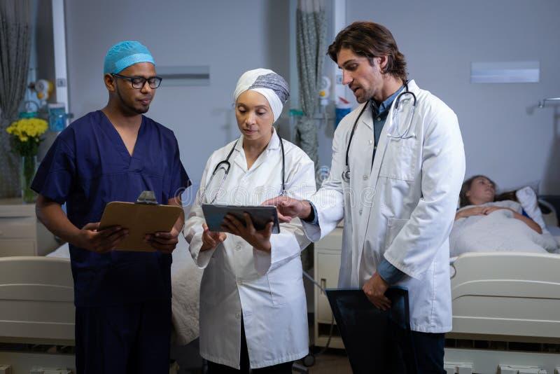 Doktorer som diskuterar över den digitala minnestavlan i klinik på sjukhuset arkivfoto