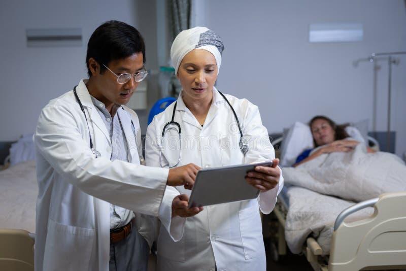 Doktorer som diskuterar över den digitala minnestavlan i klinik på sjukhuset arkivbilder