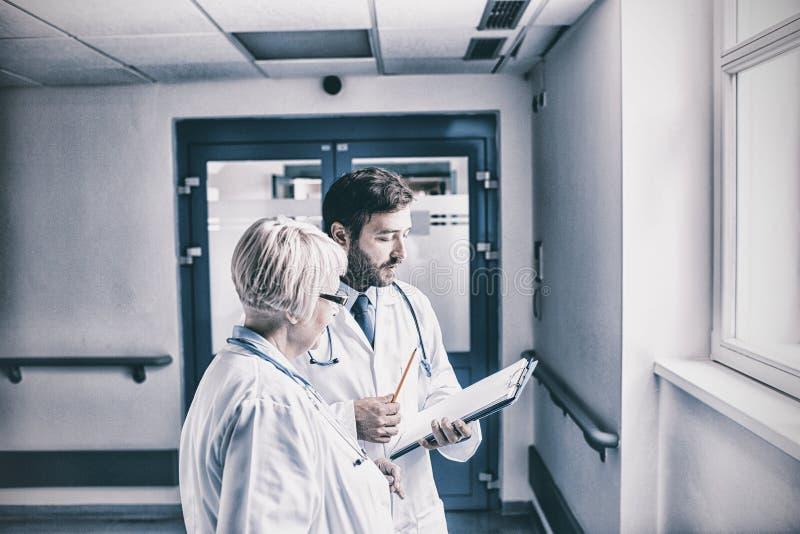 Doktorer som diskuterar över skrivplattan arkivbild