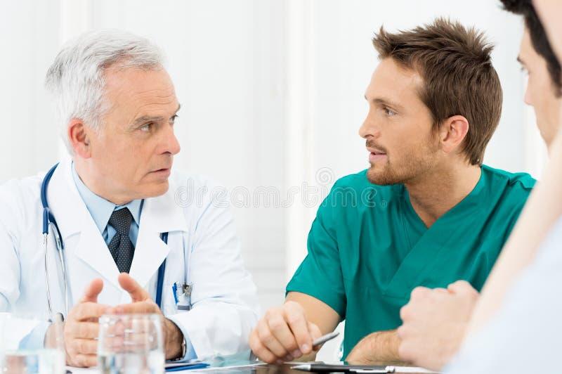 Doktorer som diskuterar i möte royaltyfria bilder