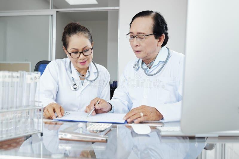Doktorer som diskuterar medicinsk historia arkivfoto