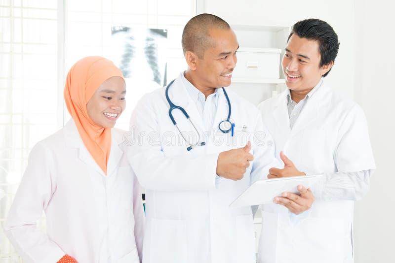 Doktorer som diskuterar på minnestavlaPC och tummar upp royaltyfri bild