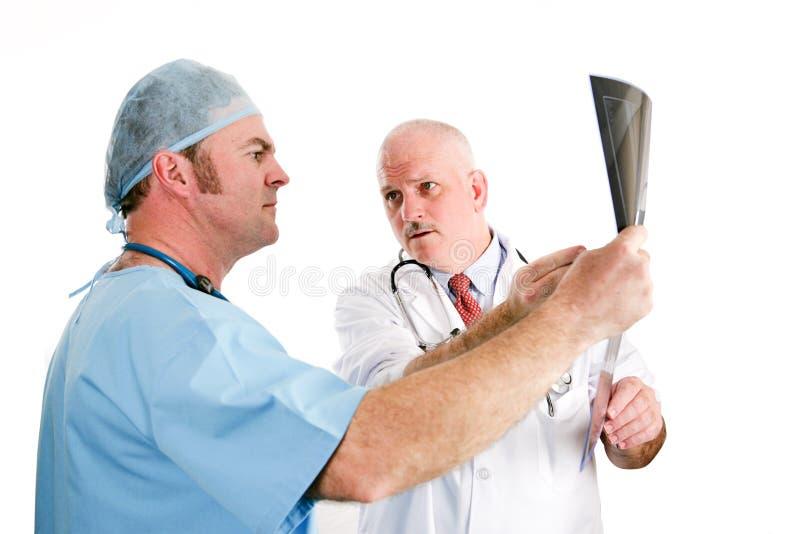 Doktorer som diskuterar röntgenstrålar royaltyfri fotografi