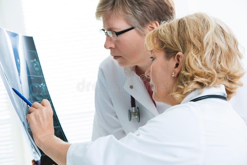 Doktorer som diskuterar röntgenstrålebild royaltyfri foto