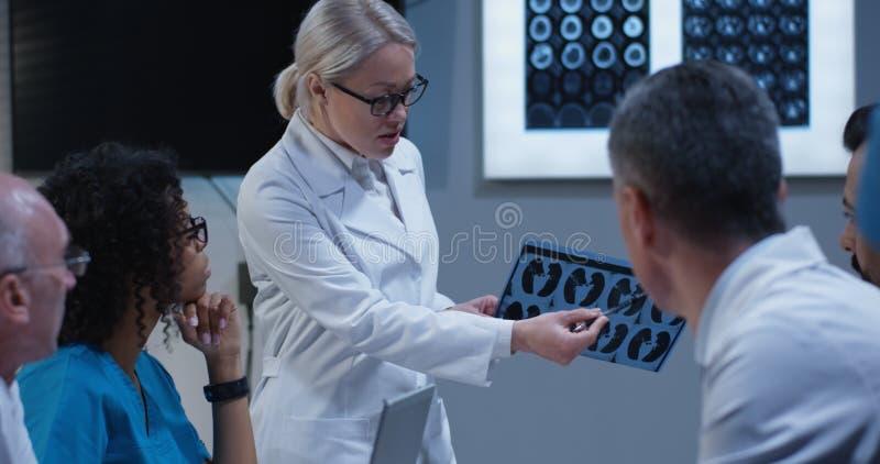 Doktorer som h?ller ?gonen p? deras kollega f?rklaring diagnos arkivfoton