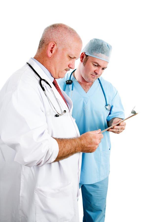 Doktorer som konsulterar sjukdomshistorien royaltyfri foto