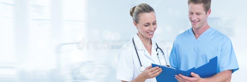 Doktorer som ser dokument mot grå bakgrund arkivbild