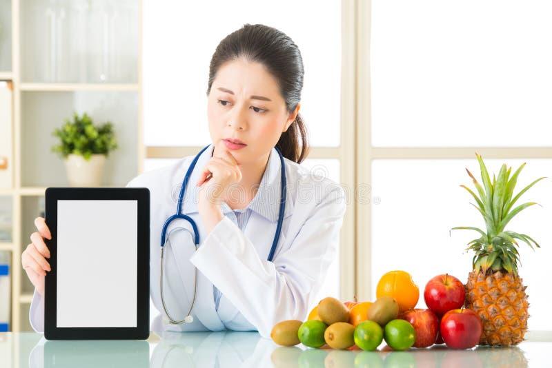 Doktorernährungswissenschaftler mit Früchten und dem Halten der digitalen Tablette fiel stockfotos