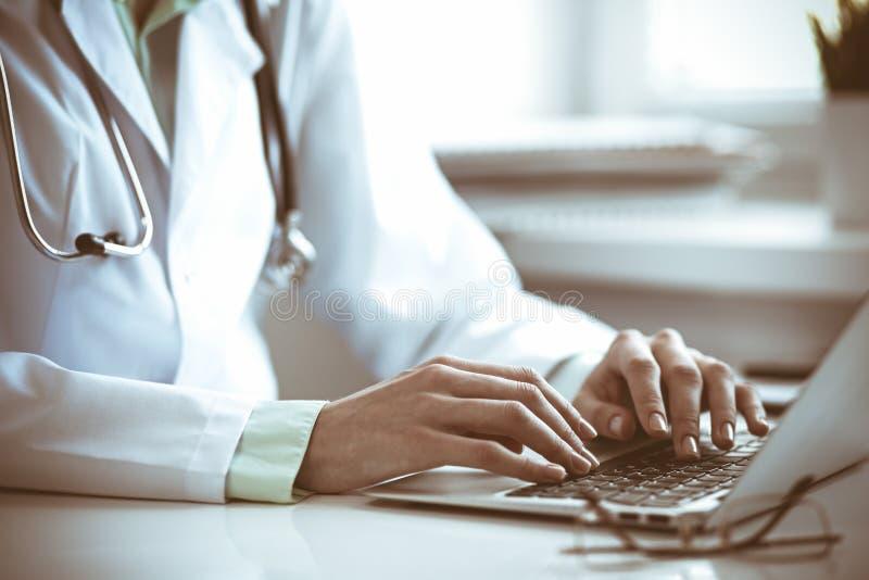 Doktorfrau, die Laptop-Computer beim Sitzen am Schreibtisch nahe Fenster im Krankenhaus verwendet Medizin- und Gesundheitswesenko lizenzfreies stockfoto
