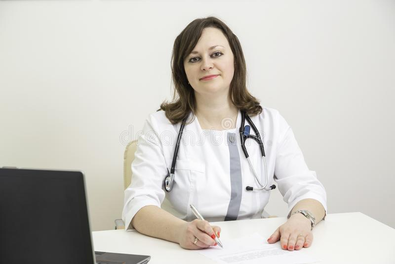 Doktorfrau am Tisch lizenzfreies stockbild