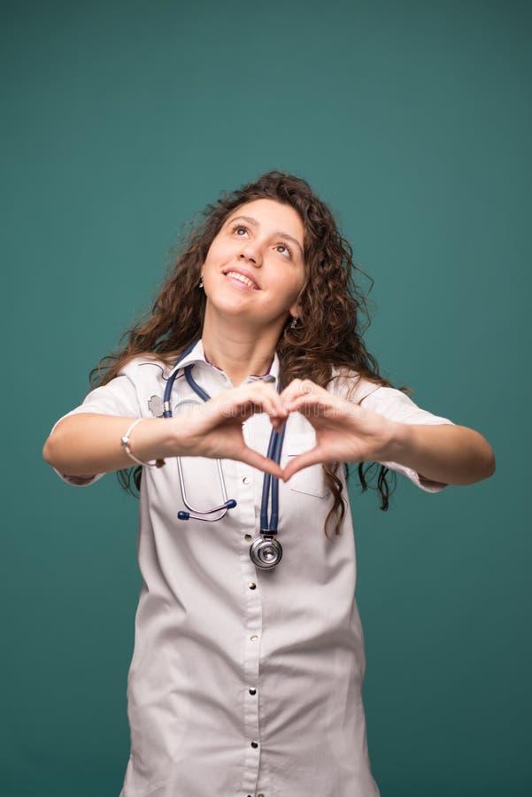 Doktorfrau zeigt gutes Zeichen auf gr?nem Hintergrund witn Kopienraum Apfel- und Bandma? Vertikales Foto stockfoto