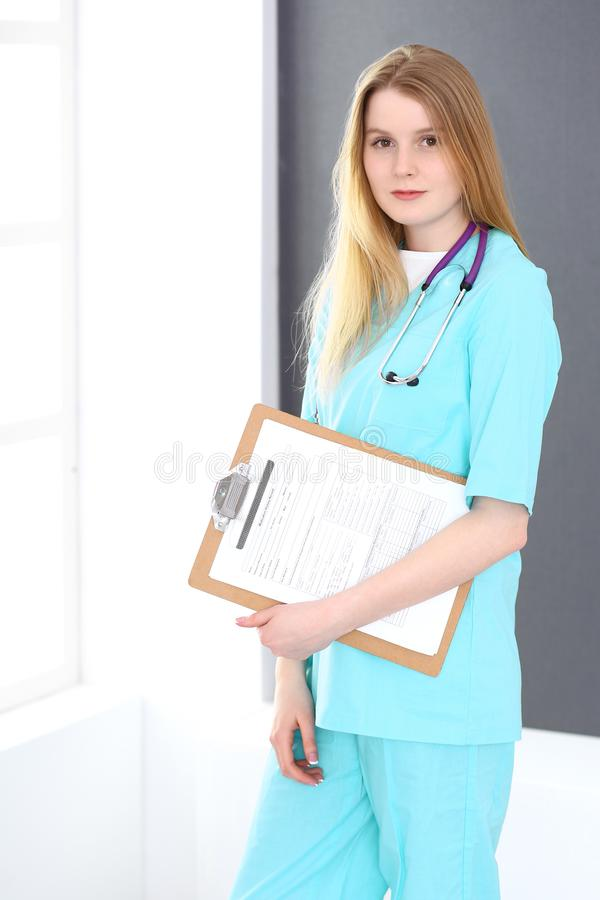 Doktorfrauenporträt mit Stethoskop Junge weibliche Chirurg- oder Krankenschwesterstellung nahe grauer Wand und Fenster in der Kli stockfoto