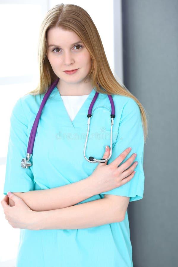 Doktorfrauenporträt mit Stethoskop Junge weibliche Chirurg- oder Krankenschwesterstellung nahe grauer Wand und Fenster in der Kli stockbild
