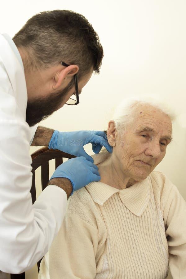 Doktorgeriater während des Test Doktors überprüft Änderungen in der Haut einer alten Frau stockfotos