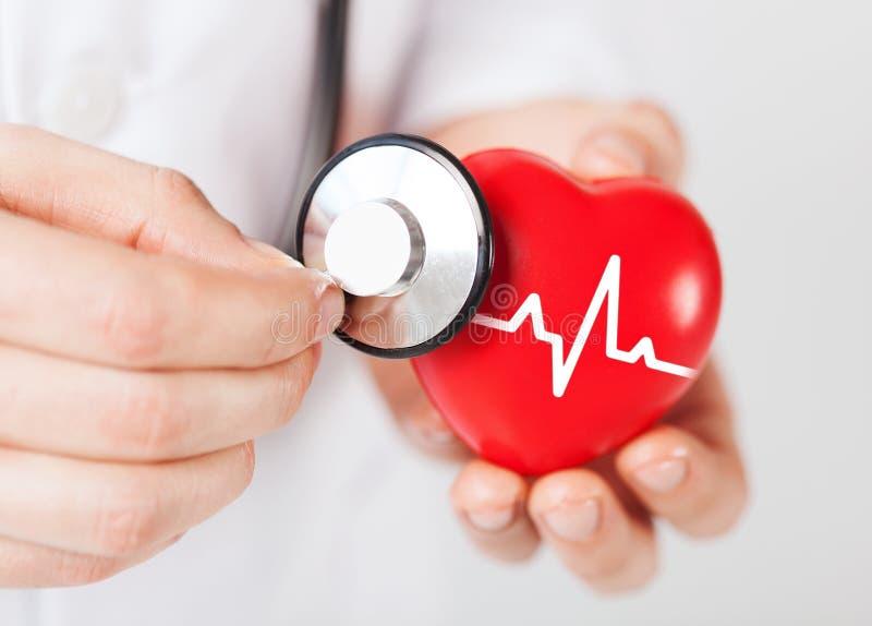 Doktorhände, die rotes Herz und Stethoskop halten stockfoto