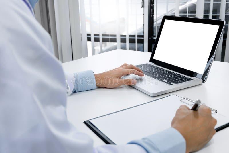 Doktorhand, die auf Tastatur mit Laptop des leeren Bildschirms schreibt stockfoto