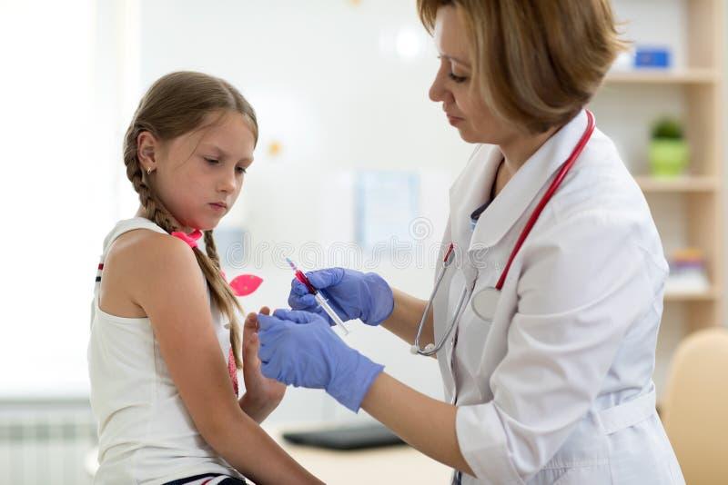 Doktorkinderarzt, der Spritze mit Einspritzungsschutzimpfung hält Mädchen hat Angst stockfotografie