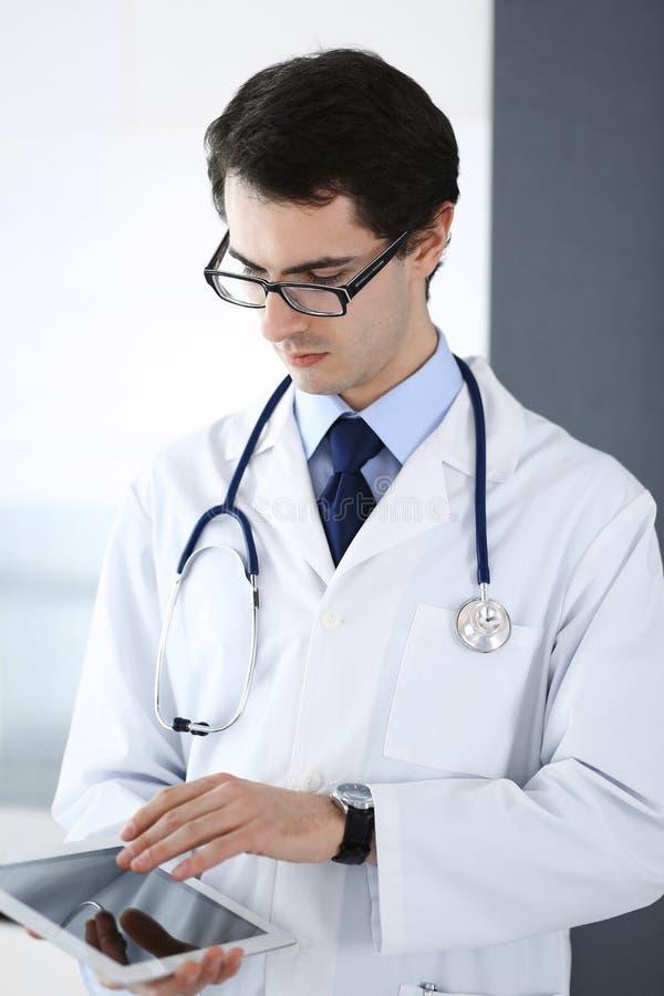 Doktormann unter Verwendung des Tablet-Computers f?r Netzforschung oder virtuelle Krankheitsbehandlung Perfekte ?rztliche Bem?hun lizenzfreie stockfotografie