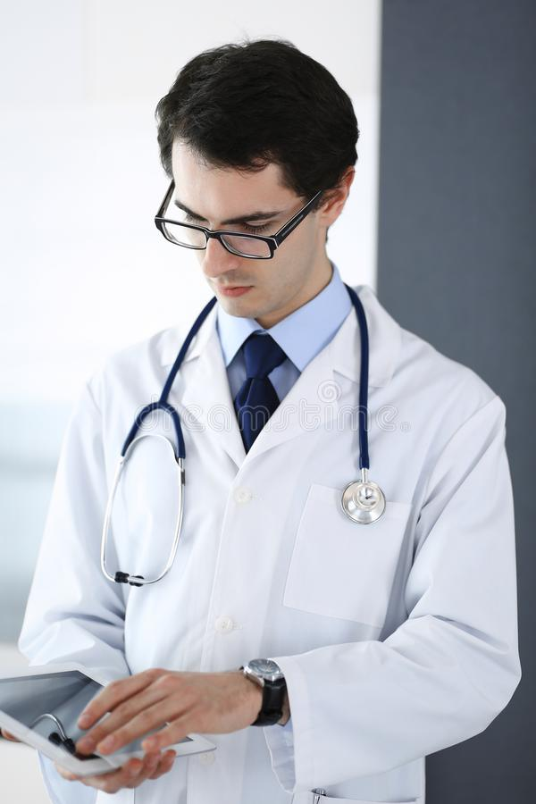 Doktormann unter Verwendung des Tablet-Computers f?r Netzforschung oder virtuelle Krankheitsbehandlung Perfekte ?rztliche Bem?hun lizenzfreies stockbild