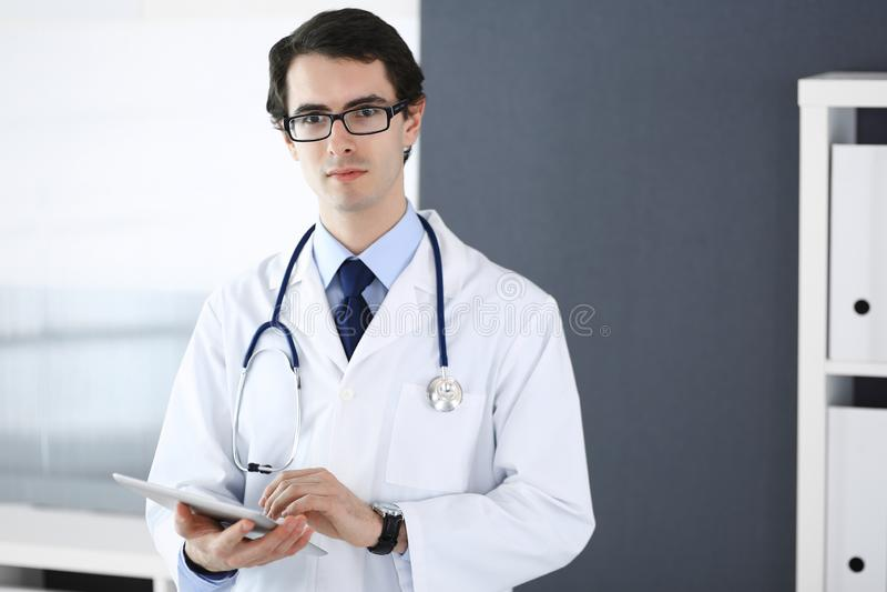 Doktormann unter Verwendung des Tablet-Computers f?r Netzforschung oder virtuelle Krankheitsbehandlung Perfekte ?rztliche Bem?hun lizenzfreie stockbilder