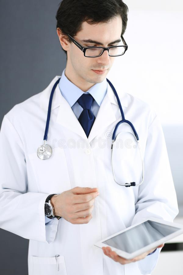 Doktormann unter Verwendung des Tablet-Computers f?r Netzforschung oder virtuelle Krankheitsbehandlung Perfekte ?rztliche Bem?hun stockfotografie
