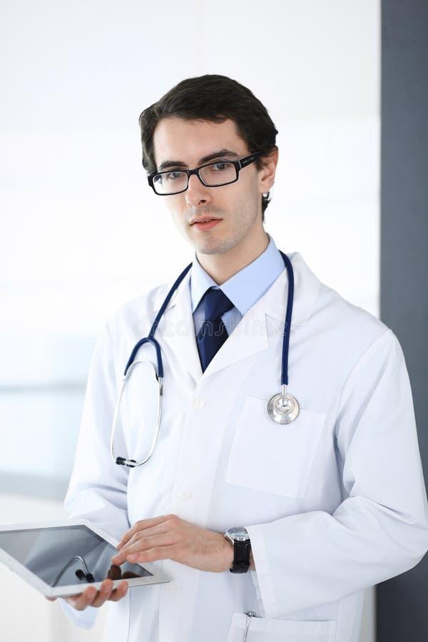 Doktormann unter Verwendung des Tablet-Computers f?r Netzforschung oder virtuelle Krankheitsbehandlung Perfekte ?rztliche Bem?hun stockfoto