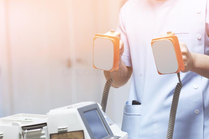 Doktorn är att ge sig defibrillators som sparar patient&en x27; s-liv i sjukhuset arkivfoton