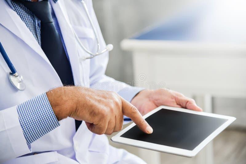 Doktorn använder den digitala minnestavlan royaltyfri fotografi