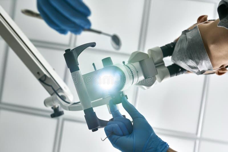 Doktorn använder det tand- mikroskopet under hans arbete royaltyfria bilder