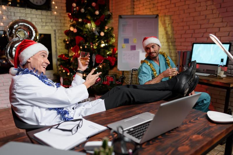Doktorn arbetar på helgdagsafton för ` s för nytt år Han rymmer ett exponeringsglas av whisky och dricker med en kollega royaltyfri foto