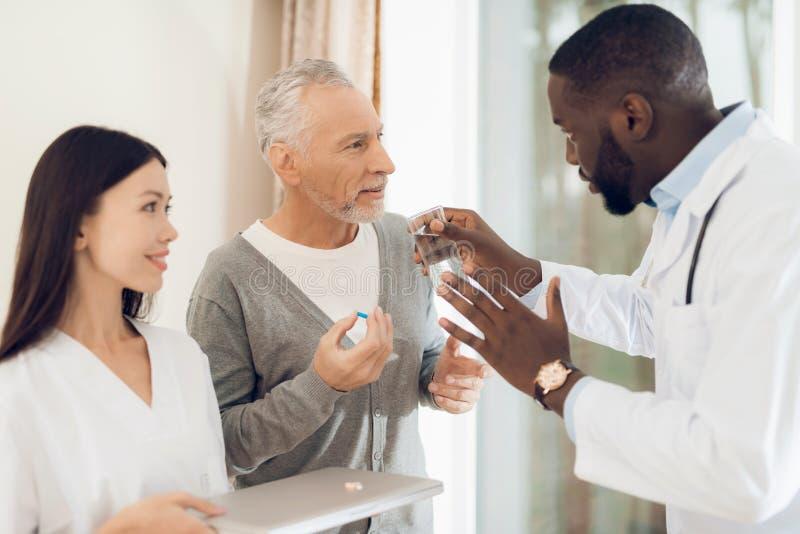 Doktorn berättar sjuksköterskan hur en äldre manlig patient bör ta preventivpillerar arkivbilder