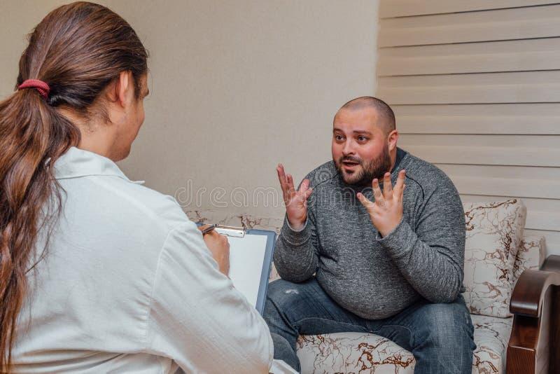Doktorn besöker hans patient Sjuk ledsen man som talar med doktorn om hans problem Doktorn skriver anmärkningar royaltyfria bilder