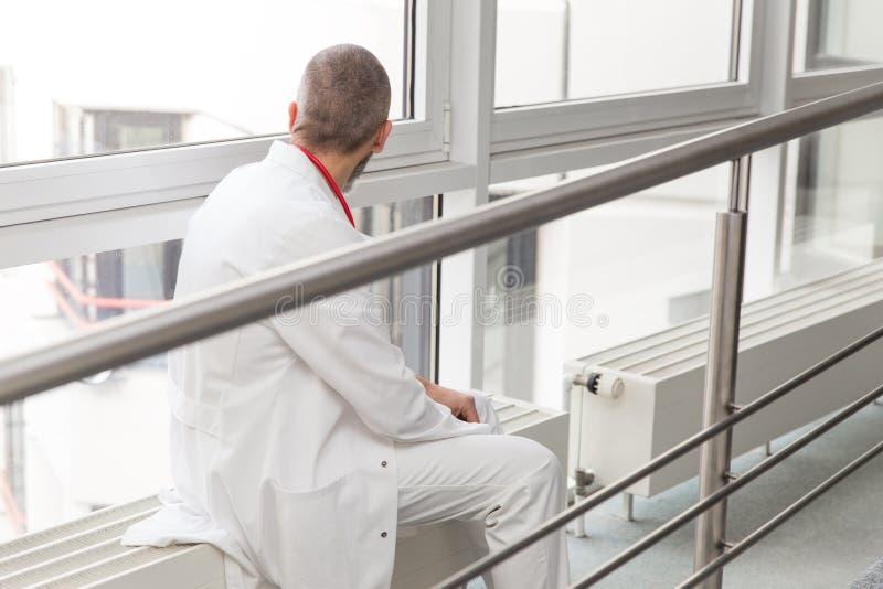 Doktorn eller kirurgen är att sitta som är thinkful på ett fönster royaltyfri bild