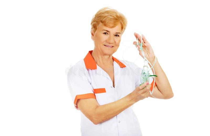 Doktorn eller sjuksköterskan för leende rymmer den äldre kvinnliga syremaskeringen arkivfoton