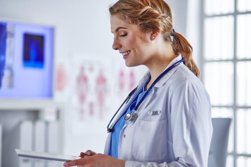 Doktorn f?r den unga kvinnan st?r med br?det med skrivplattan som ler i sjukhuskontor royaltyfria foton