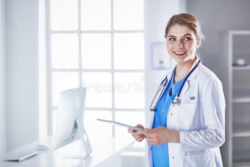 Doktorn för den unga kvinnan står med brädet med skrivplattasmilin arkivfoton