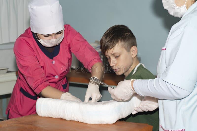 Doktorn förbinder en bruten arm till en pojke royaltyfri foto