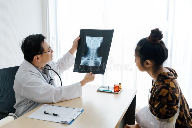 Doktorn förklarar om hjärnröntgenstråleresultaten till en kvinnlig patient i hans kontor på sjukhus royaltyfria foton