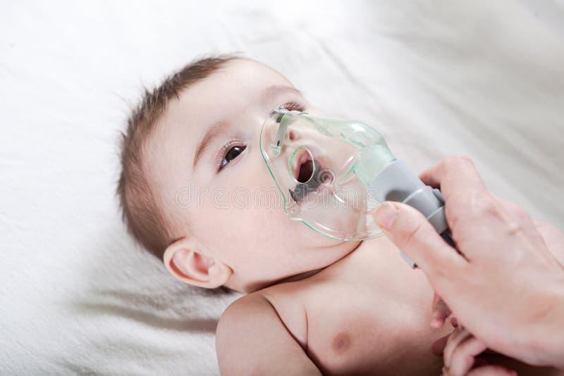 Doktorn gör inandning till ett sjukt litet att behandla som ett barn arkivfoton