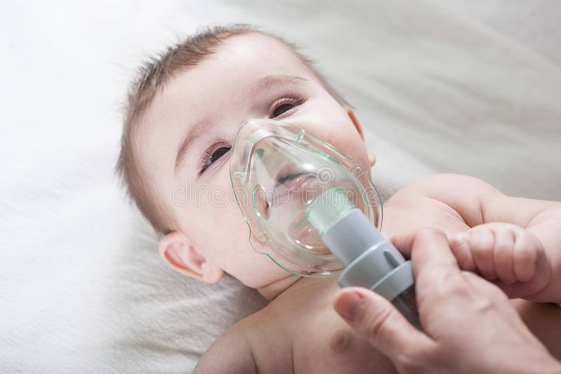 Doktorn gör inandning till ett sjukt litet att behandla som ett barn fotografering för bildbyråer