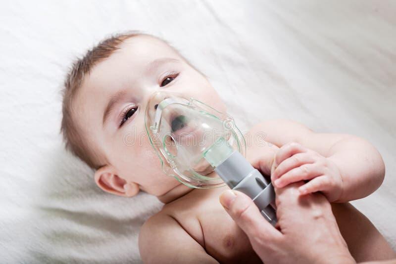 Doktorn gör inandning till ett sjukt litet att behandla som ett barn royaltyfri foto