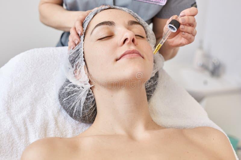 Doktorn gör kosmetologtillvägagångssättet, applysvitaminserum för att vända mot av den härliga kvinnan, klient av cosmetologyklin royaltyfri fotografi