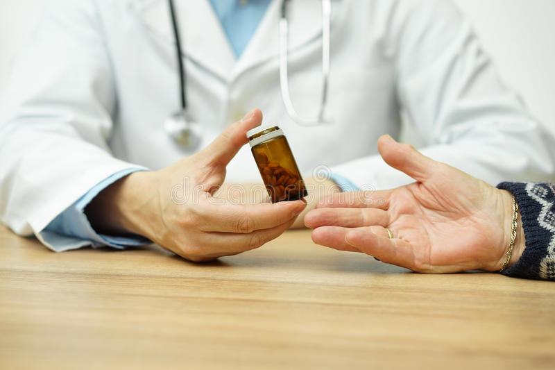 Doktorn ger flaskan av preventivpillerar till en gammal kvinnlig patient arkivbilder