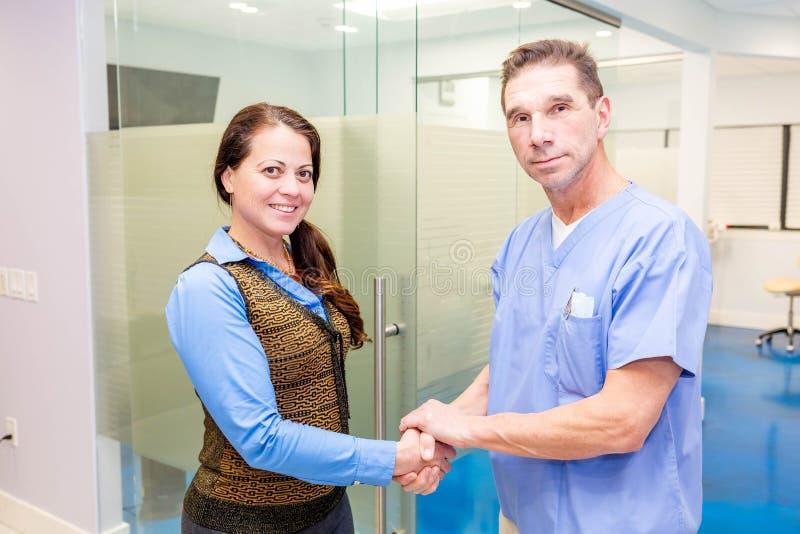 Doktorn hälsar den kvinnliga patienten på sjukhuskontoret royaltyfri foto
